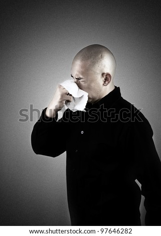 A man sneezing into a tissue - stock photo