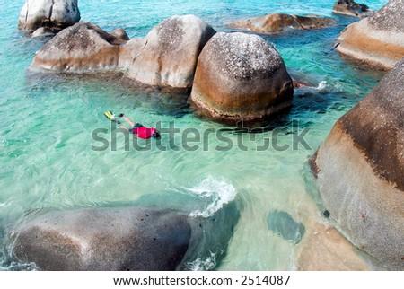 A man snorkeling at The Baths on Virgin Gorda in the British Virgin Islands. - stock photo
