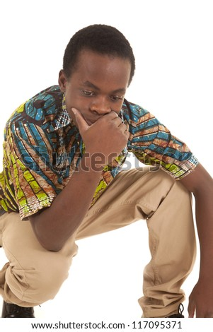 A man squatting down with a serious expression on his face thinking. - stock photo