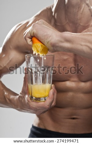 a man squeezing orange juice to glass - stock photo