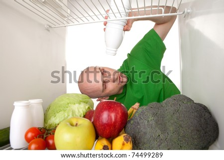 A man standing at the door of a refrigerator with fresh fruits and vegetables, holding an empty white bottle or container.