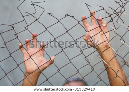 A man standing behid the grid fence