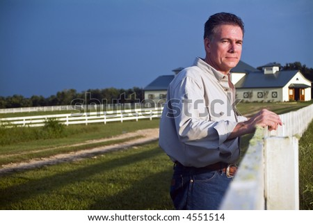 A man standing by a long white wooden fence bathed in the light of late afternoon sun. - stock photo
