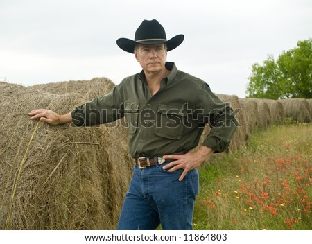 A man standing by a row of large round bales of hay. - stock photo