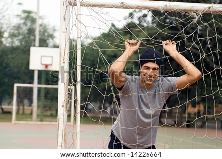 A man standing, holding onto a soccer goal net, smiling. - horizontally framed - stock photo
