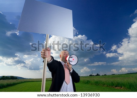 A man standing in a green field, holding a blank sign and shouting through a megaphone. - stock photo