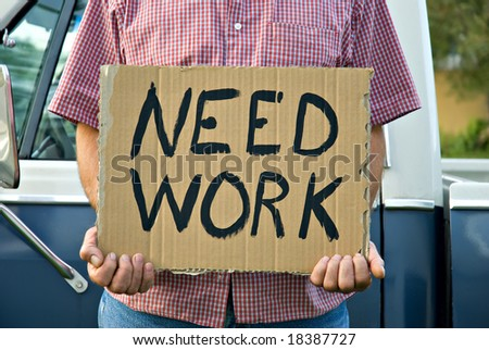 A man standing in front of an old pickup truck holding a sign begging for work. - stock photo
