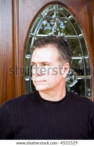 A man standing in front of an ornate door gazing peacefully off into the distance. - stock photo