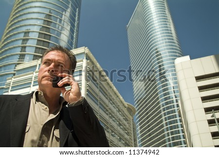 A man standing in front of some some towering office building talking on a cell phone.