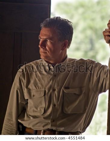 A man standing in the open door of a dark room. - stock photo