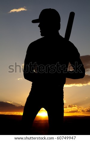 A man standing in the sunset holding his bat. - stock photo