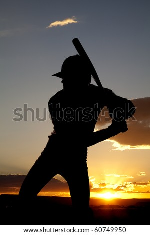 A man standing in the sunset holding his bat ready to swing - stock photo