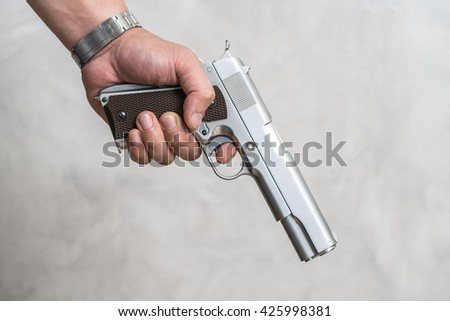 A man standing on a criminal with a gun in his hand. - stock photo