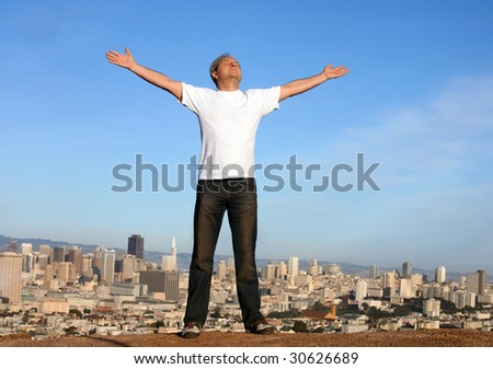 A man standing on a hill with a view of San Francisco, his arms raised. - stock photo