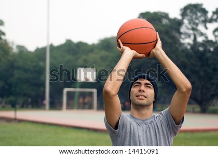 A man, standing tall, preparing to shoot a basketball while half-smiling, in a park - horizontally framed - stock photo