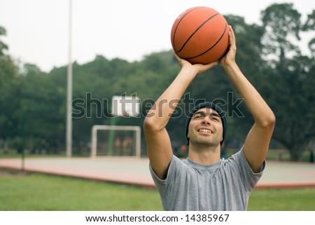 A man, standing tall, preparing to shoot a basketball while smiling, in a park - horizontally framed - stock photo