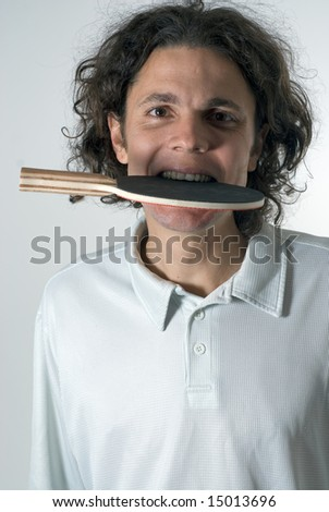 A man, standing, wearing a white polo, bites a ping pong paddle while looking at the camera. Vertically framed shot. - stock photo