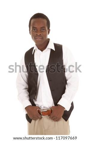 A man standing with a small smile on his lips holding on to his belt - stock photo