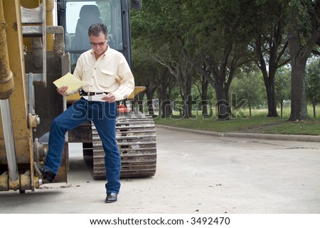 A man standing with his foot on the bucket of an idle backhoe with documents in his hand. - stock photo