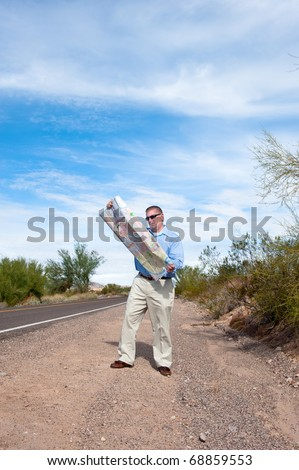 A man stands along a deserted road reading a roadmap - stock photo