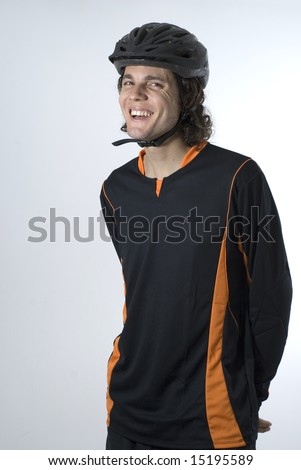 A man stands in a black and orange biking outfit and helmet, smiling at the camera. Vertically framed shot. - stock photo