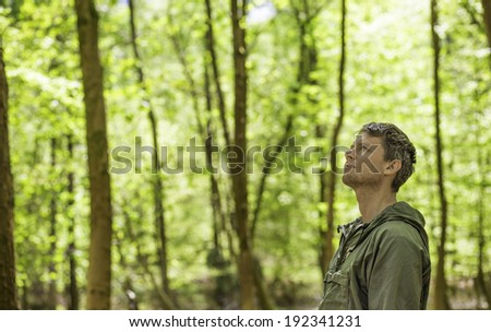A man stands in a forest looking up and smiling. - stock photo