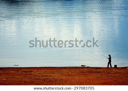 A man stands in front of the river to angle the fish with yellow sky reflecting on the water - stock photo