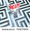A man stands lost in the middle of a large, confusing maze or labyrinth and holds a sign reading Help - stock photo