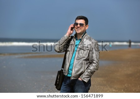 A man stands on the beach and talking on the phone