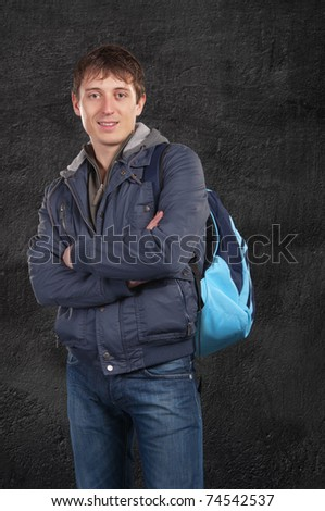 A man stands with a backpack on his shoulder. On the background wall - stock photo
