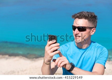 A man surfing the Internet in the phone in front of the sea - stock photo