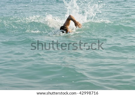 A man swimming front crawl in the sea. - stock photo