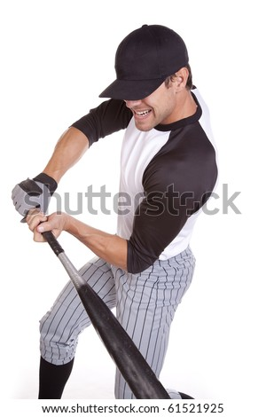 A man swinging his bat hard at the ball that is coming. - stock photo