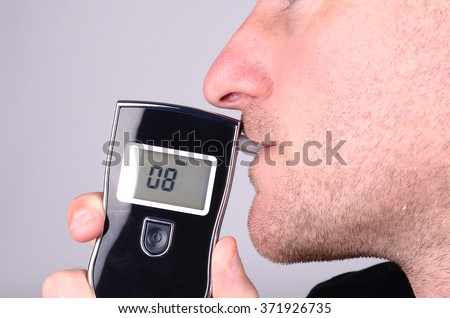 A man takes a breathalyser test - stock photo