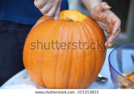 A man takes out the fibrous insides and seeds from a pumpkin before carving a jack o' lantern. - stock photo