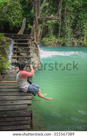 A man taking a photo by mobile phone at the river - stock photo