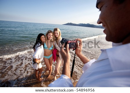 A man taking a photo of three women at the ocean. - stock photo