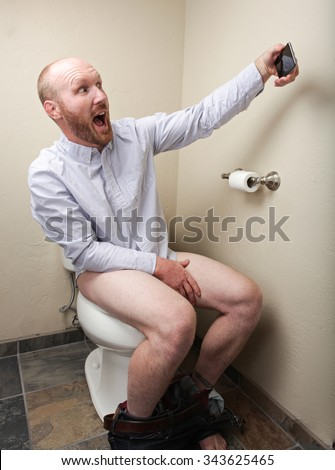 A man taking a selfie while in the bathroom on the toilet - stock photo