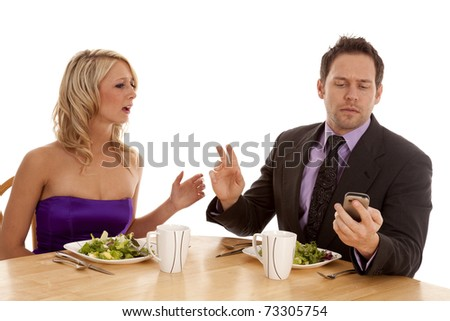 A man telling his date to hold on while he checks his phone for a text message. - stock photo