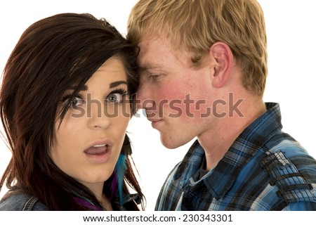 A man telling his woman a secret she has a shocked expression. - stock photo