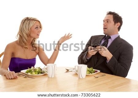 A man texting during his date and the woman is not very happy. - stock photo
