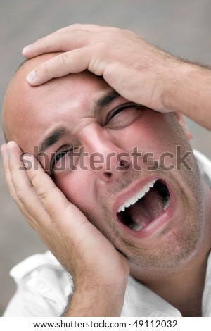 A man that looks distraught and mentally overloaded grabs his bald head in agony and desperation. Shallow depth of field. - stock photo