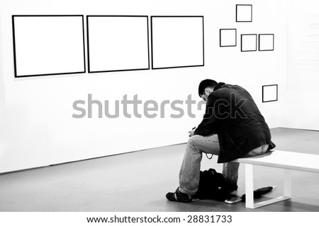 A man thinking and pondering at a photographic exhibition's gallery - stock photo