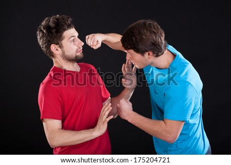 A man threatening the other one with a fist