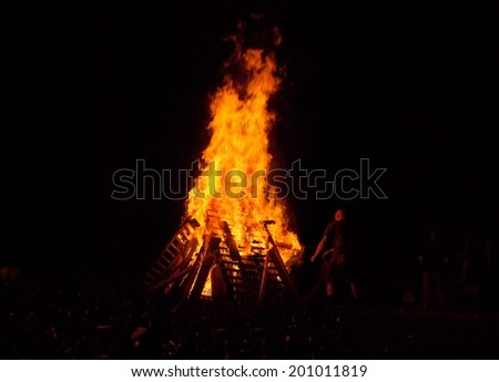 A man throws wood into a glowing red, orange, and yellow bonfire in the dark night. - stock photo