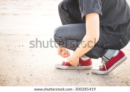A man tie his sneaker shoes with sunlight - stock photo