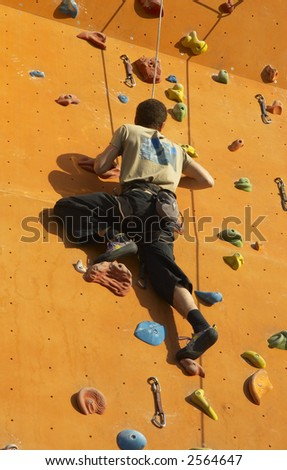 a man training on a climbing wall - stock photo