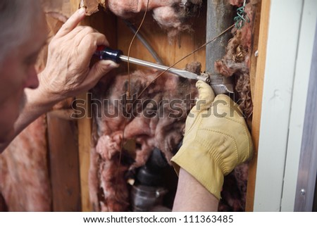 a man tries to repair a broken pipe in his house wall