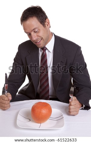 A man trying to be healthy and getting ready to dig into a orange on his plate. - stock photo