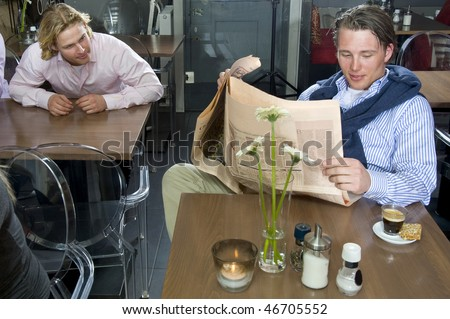 A man trying to catch a glimpse at the paper of a man sitting at another table - stock photo